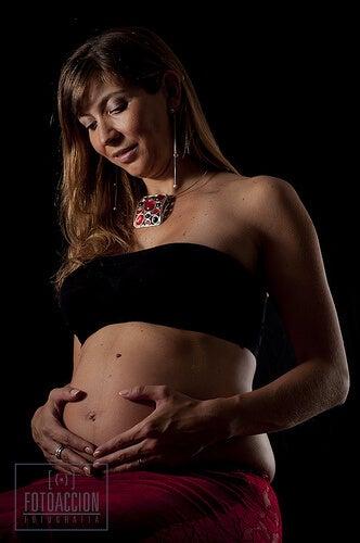 Kvinde der holder sine haender paaa sin gravide mave