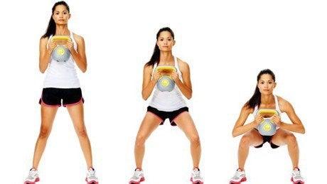 Kvinde der laver squat med kettlebell
