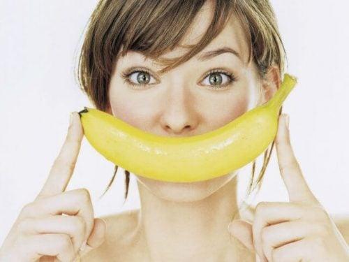Kvinde der holder en banan for munden