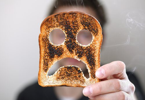 Person der holder et stykke toastbroed med en sur smiley