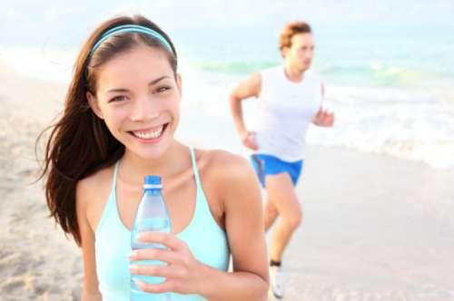 Kvinde der smiler og drikker vand