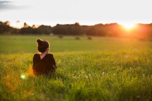 Kvinde der sidder udenfor og ser paa solen