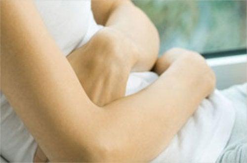 Kvinde der holder sig for maven - inflammation og gigt