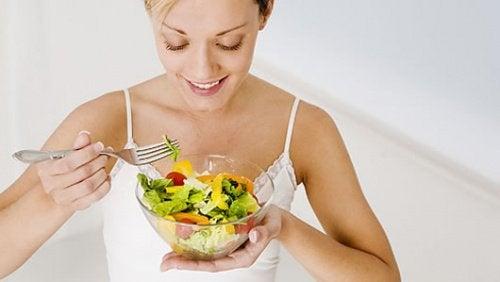 Kvinde der spiser en salat
