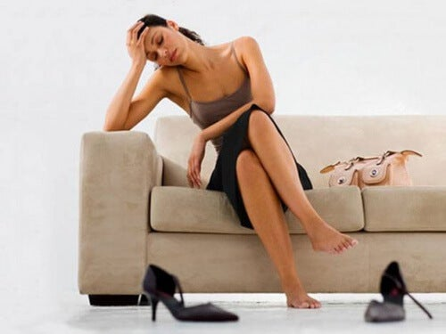 Kvinde der sidder paa sofaen og er traet
