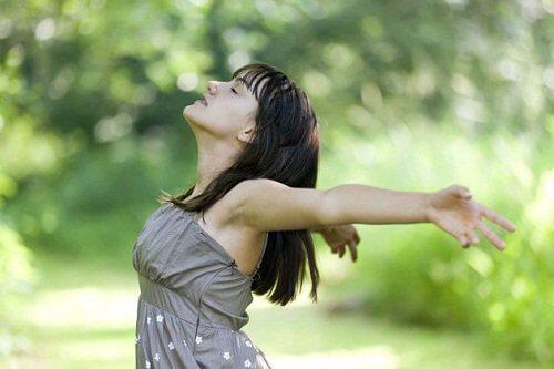Kvinde der staar med spredte arme og traekker vejret dybt