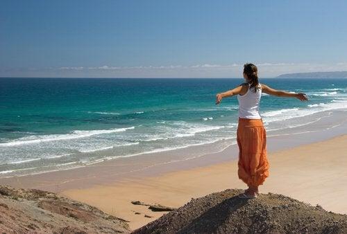Kvinde der staar med spredte arme ved en strand
