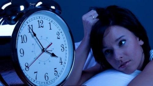 Kvinde der ligger og stirrer paa et ur
