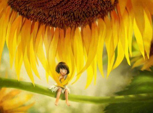 Lille pige der sidder under en stor blomst