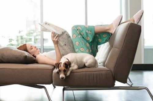 Kvinde der laeser paa en sofa