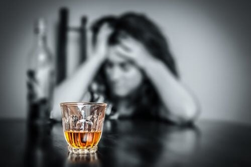 Kvinde der sidder ved bordet med et glas alkohol