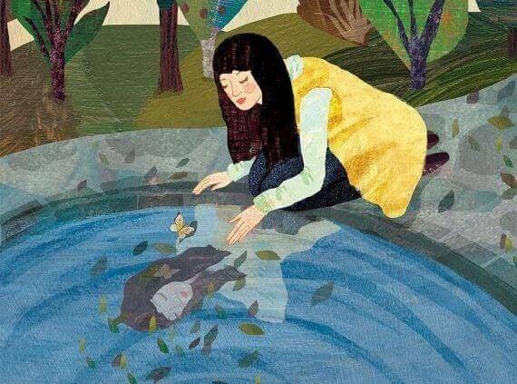 Kvinde der ser hendes spejlbillede i vand
