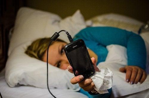Kvinde der ligger med sin telefon i sengen