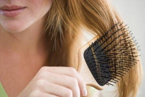 Kvinde der foerer en boerste gennem haaret