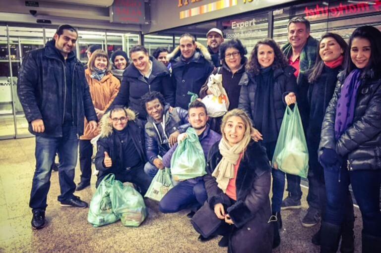 Mange mennesker med poser med varer - madspild i supermarkeder
