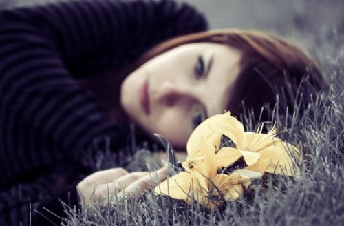 Ung kvinde der ligger paa noget graes med angst