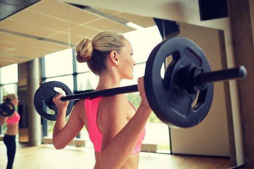 Kvinde der laver squat med vaegtstang