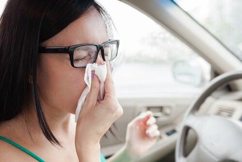 Kvinde der pudser naese i bilen