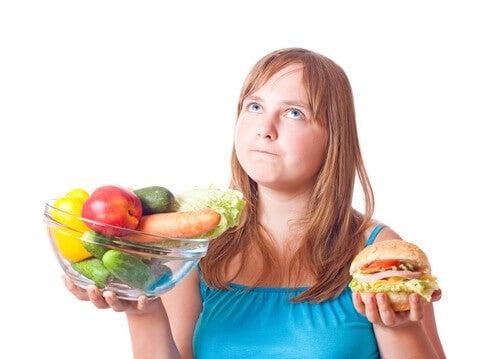 Ung kvinde der staar med groentsager og en burger