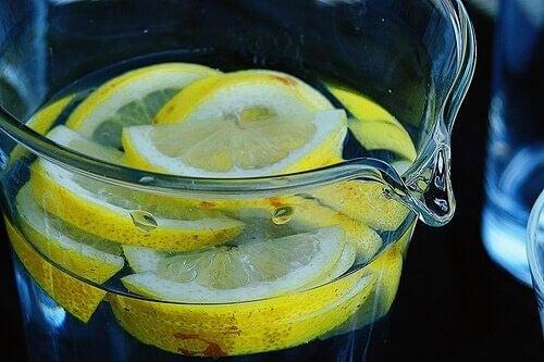 Citronskiver i kande med vand.