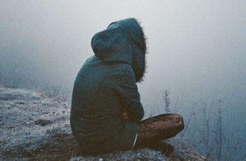 Person der sidder paa kanten af en bakke og ser ud