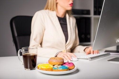 Kvinde der spiser donuts mens hun arbejder