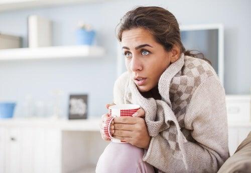 Kvinde fryser under tæppe