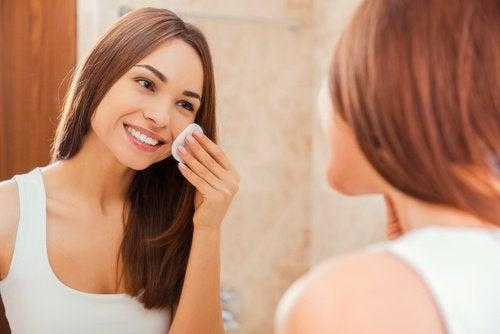 Kvinde der ser sig selv i spejlet mens hun ordner sin hud