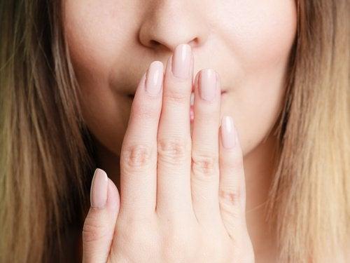 Kvinde har sin hånd over sin mund.