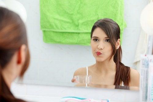 Ung kvinde der ser sig selv i spejlet