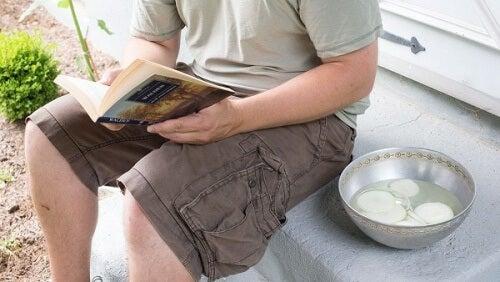 Mand der sidder og laeser med en skaal med loeg
