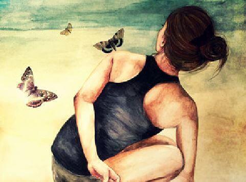 Kvinde der sidder med sommerfugle