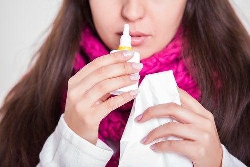 Kvinde der bruger naesespray mod en tilstoppet næse