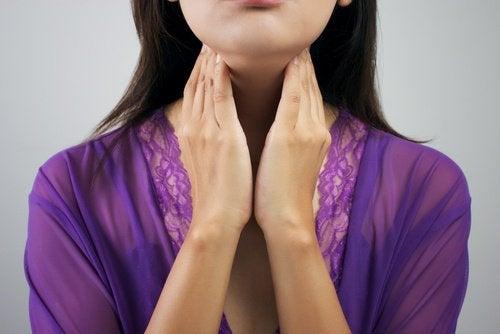 Kvinde der holder paa sin hals