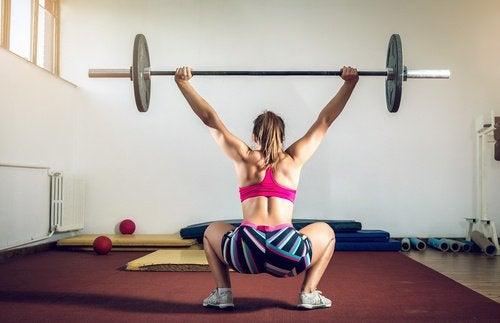 Kvinde der laver sumo squat med vaegtstang