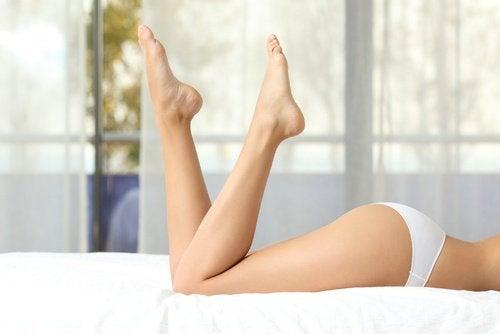 Nedre halvdel af en kvinde der ligger paa en seng