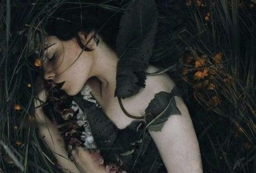 Kvinde der ligger med nogle blade over sig