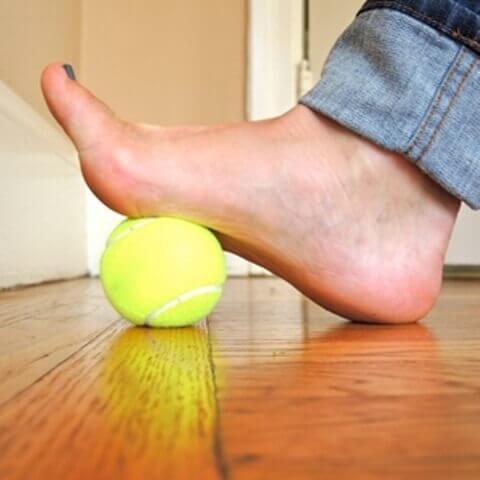 Person der traeder paa en tennisbold