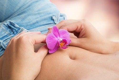 Kvinde der holder en blomst paa sin mave