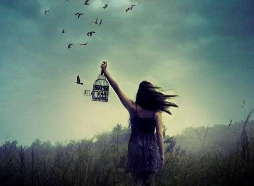 Kvinde der holder et fuglebur og saetter fuglene fri