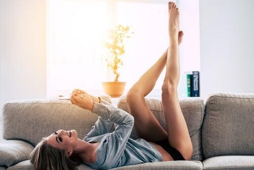 Glad kvinde der ligger paa sofaen