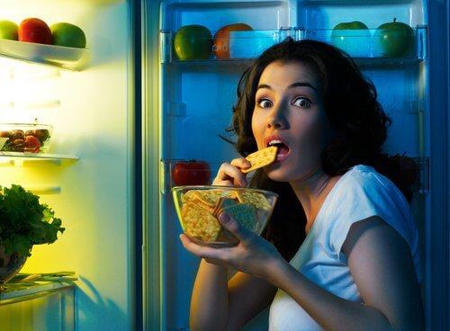 Kvinde der snacker fra koeleskabet