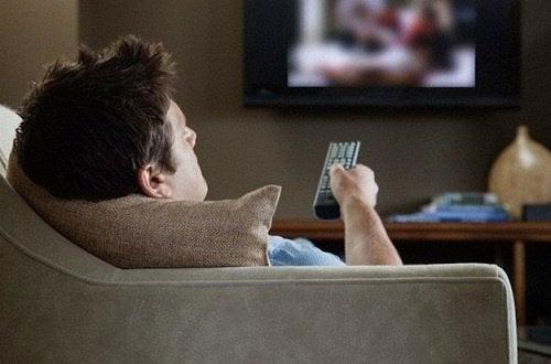 Mand der sidder i sofaen foran tv'et