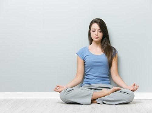 Kvinde der sidder i lotus stilling