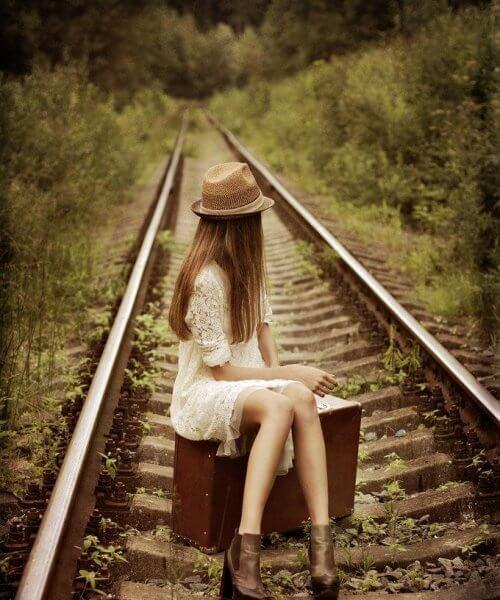 Pige der sidder paa en kuffert mellem togskinner