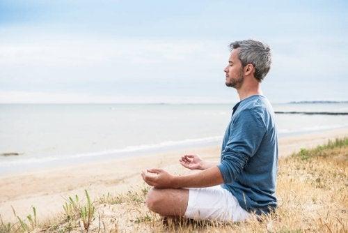 Mand der mediterer ved vandet