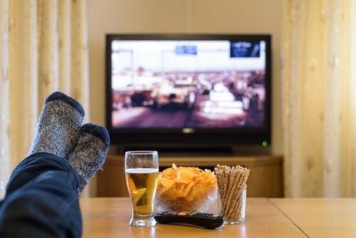 Mand der ser tv med oel og chips