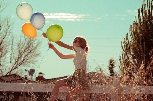 Ung kvinde der holder balloner