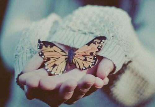 Pige der holder en sommerfugl i haenderne