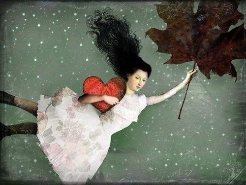Kvinde der holder et stort blad og et hjerte